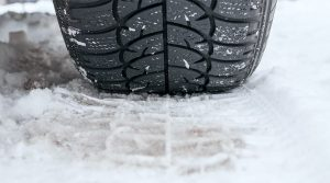 A close up of a tire making a tread in heavy snow.