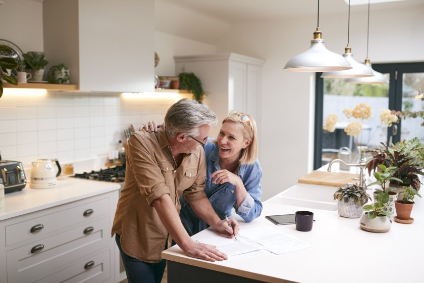 Mature couple laughing and signing documents at their kitchen island.